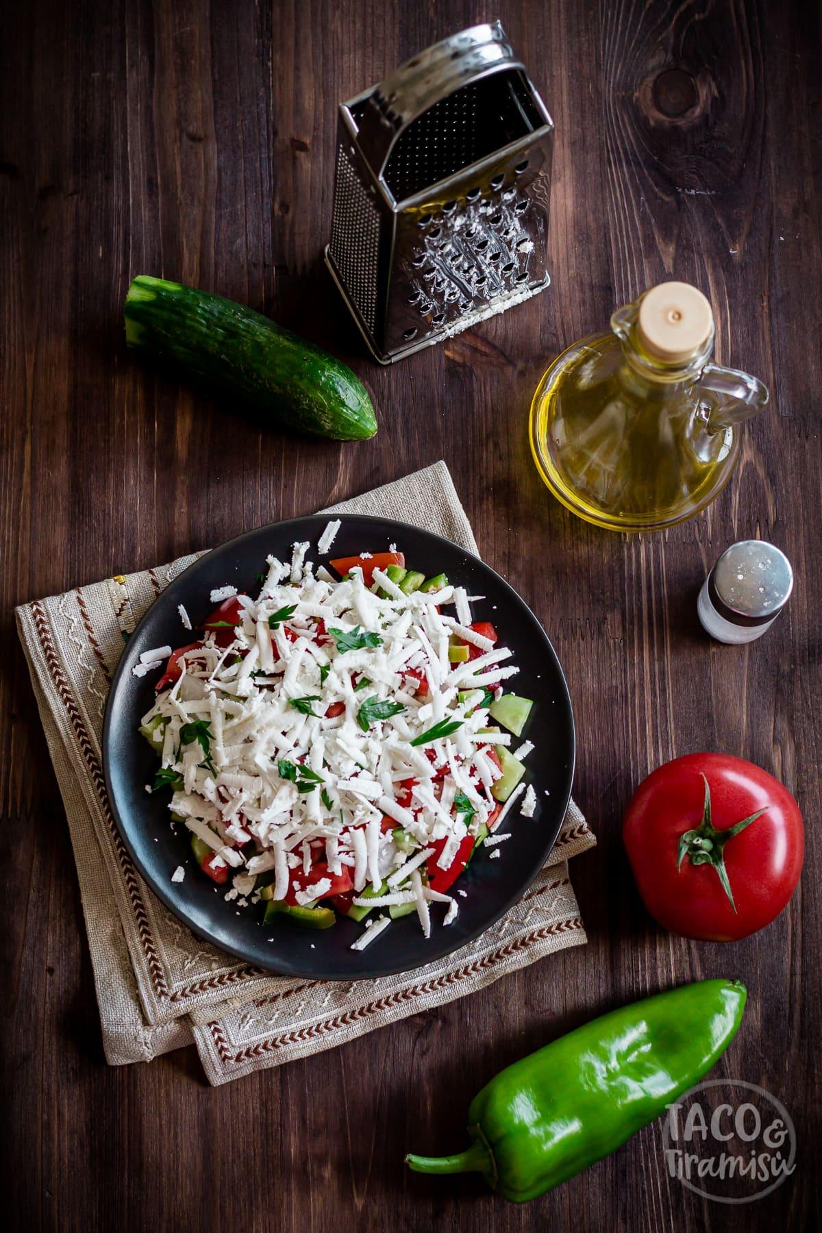 shopska salad served in a black plate with vegetables, oil and a grater aside
