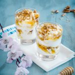 two glasses of yogurt honey and walnut dessert on a white napkin with ping flowers
