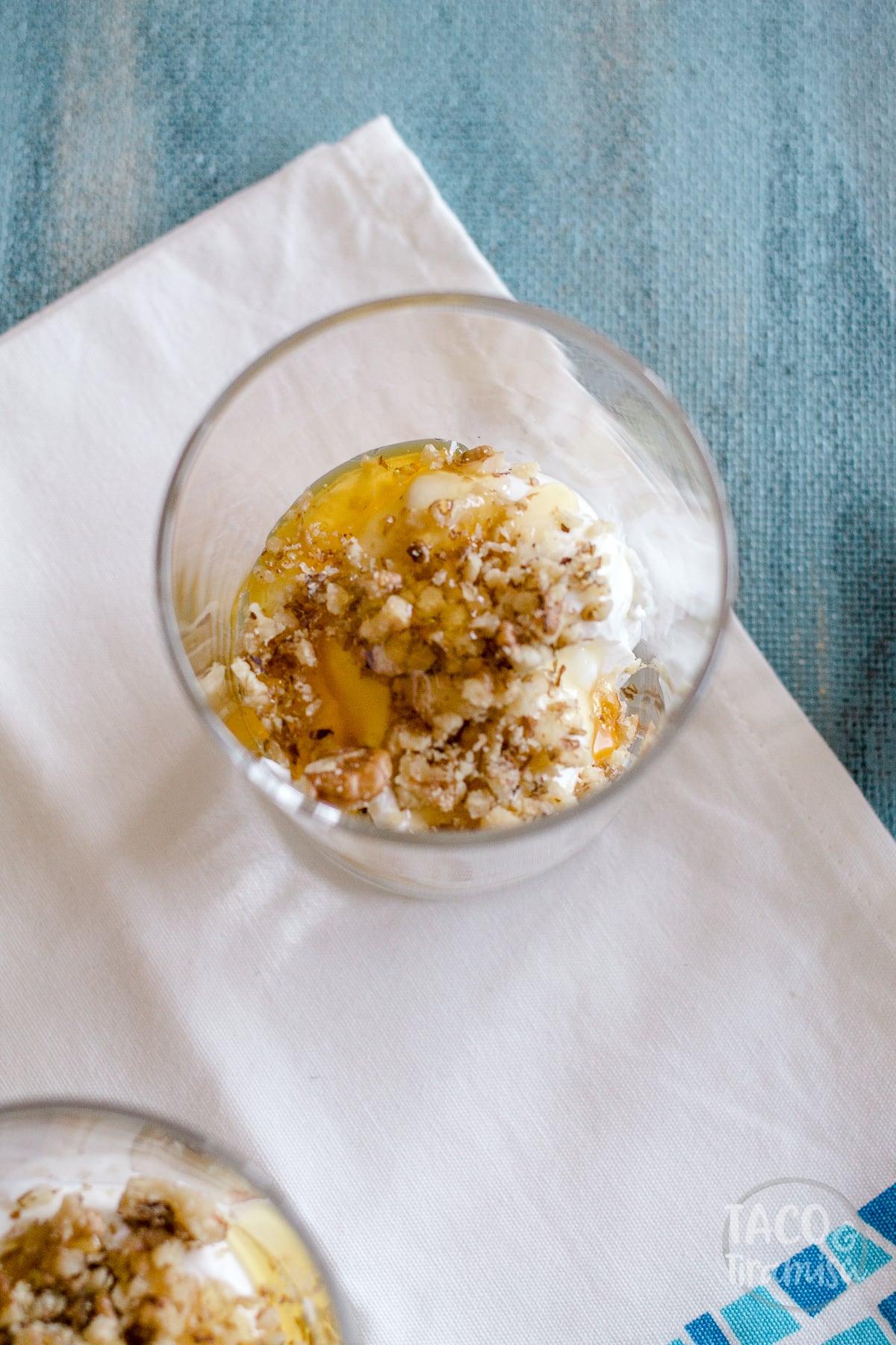 a glass half full of yogurt, honey and walnuts, flat lay
