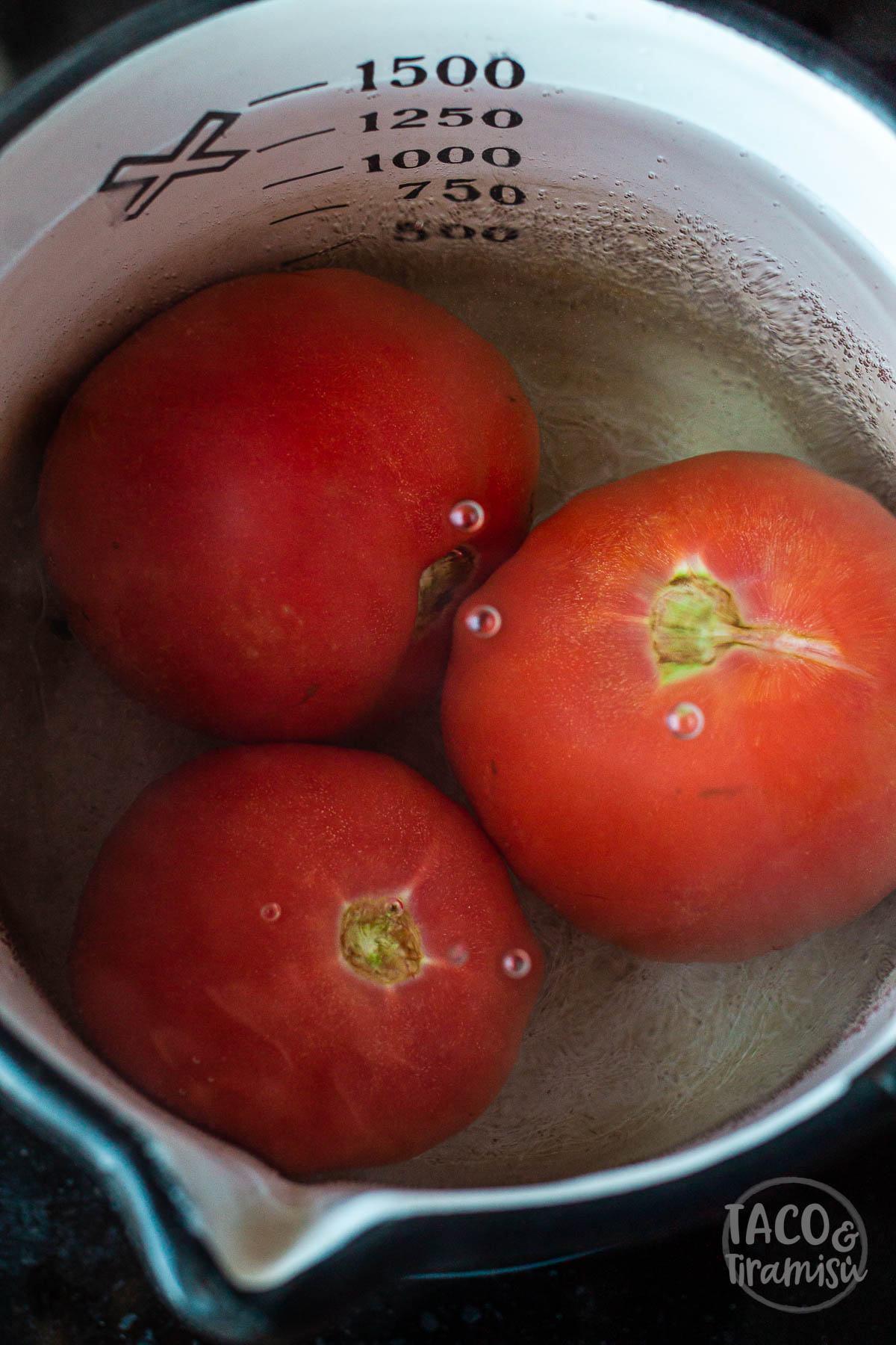 tomatoes submurged in a pot with water