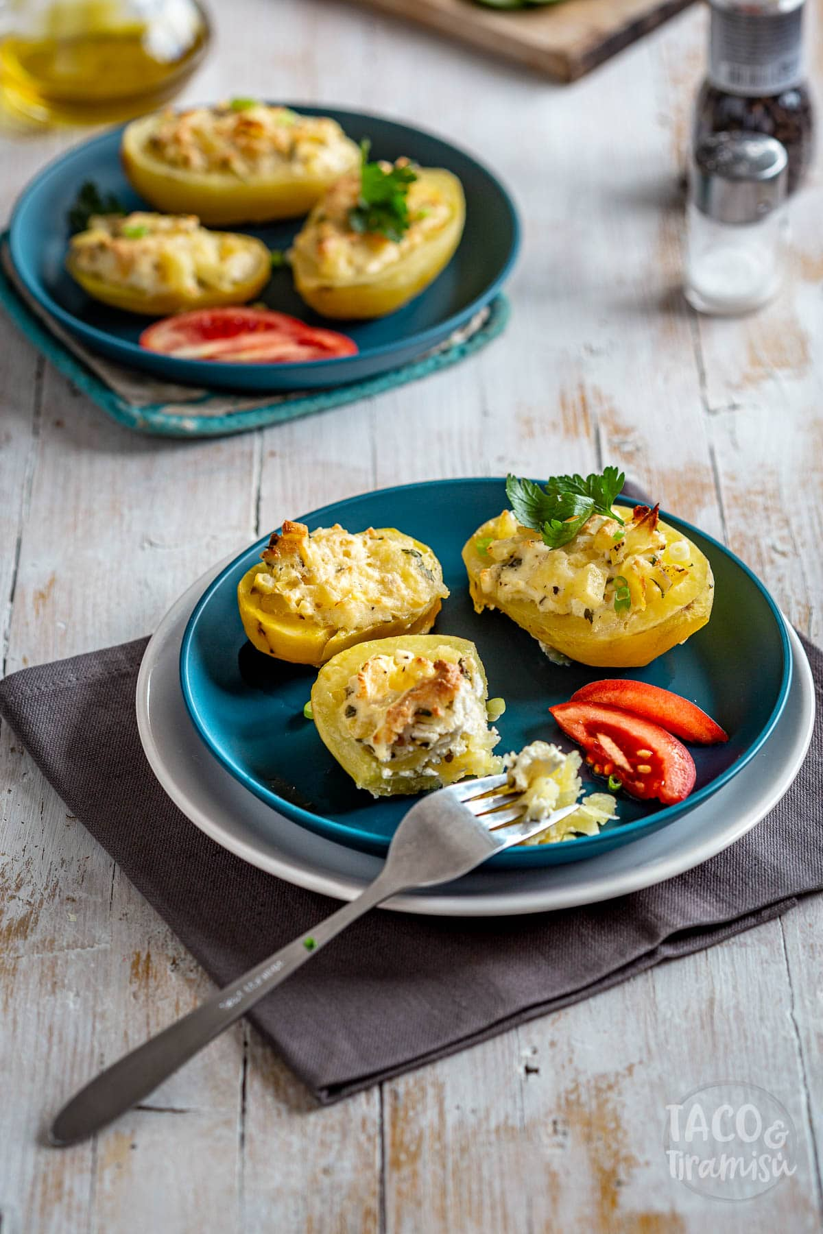 cheese stuffed potatoes served in two plates with tomatoes and a fork taking out of one potato