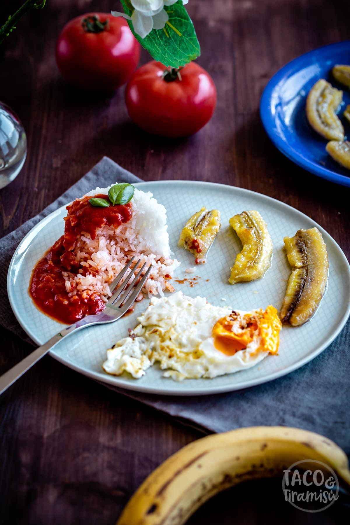 arroz a la Cubana in a plate being eaten with a fork inside