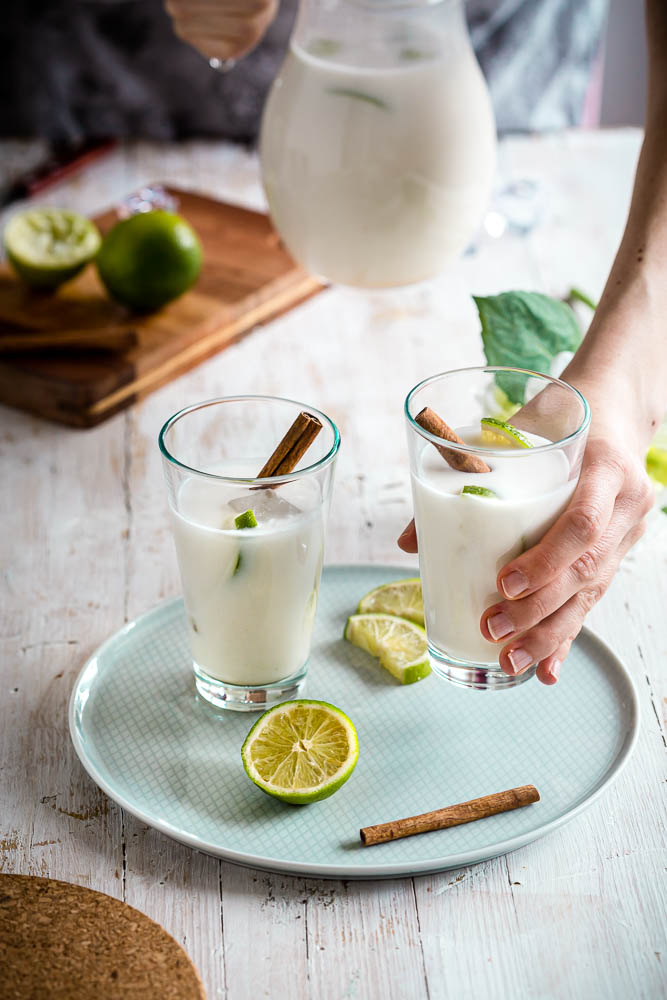 two glasses of coconut horchata on a plate with lime and cinnamon aside