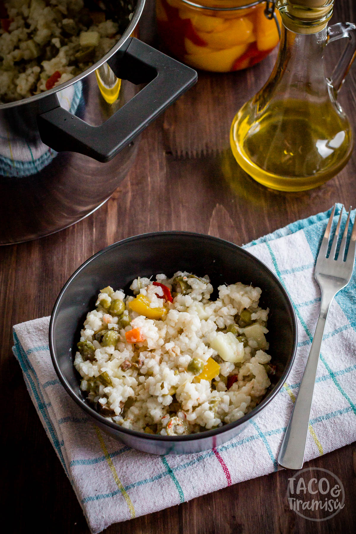 italian rice salad in a black bowl next to olive oil and pickled peppers