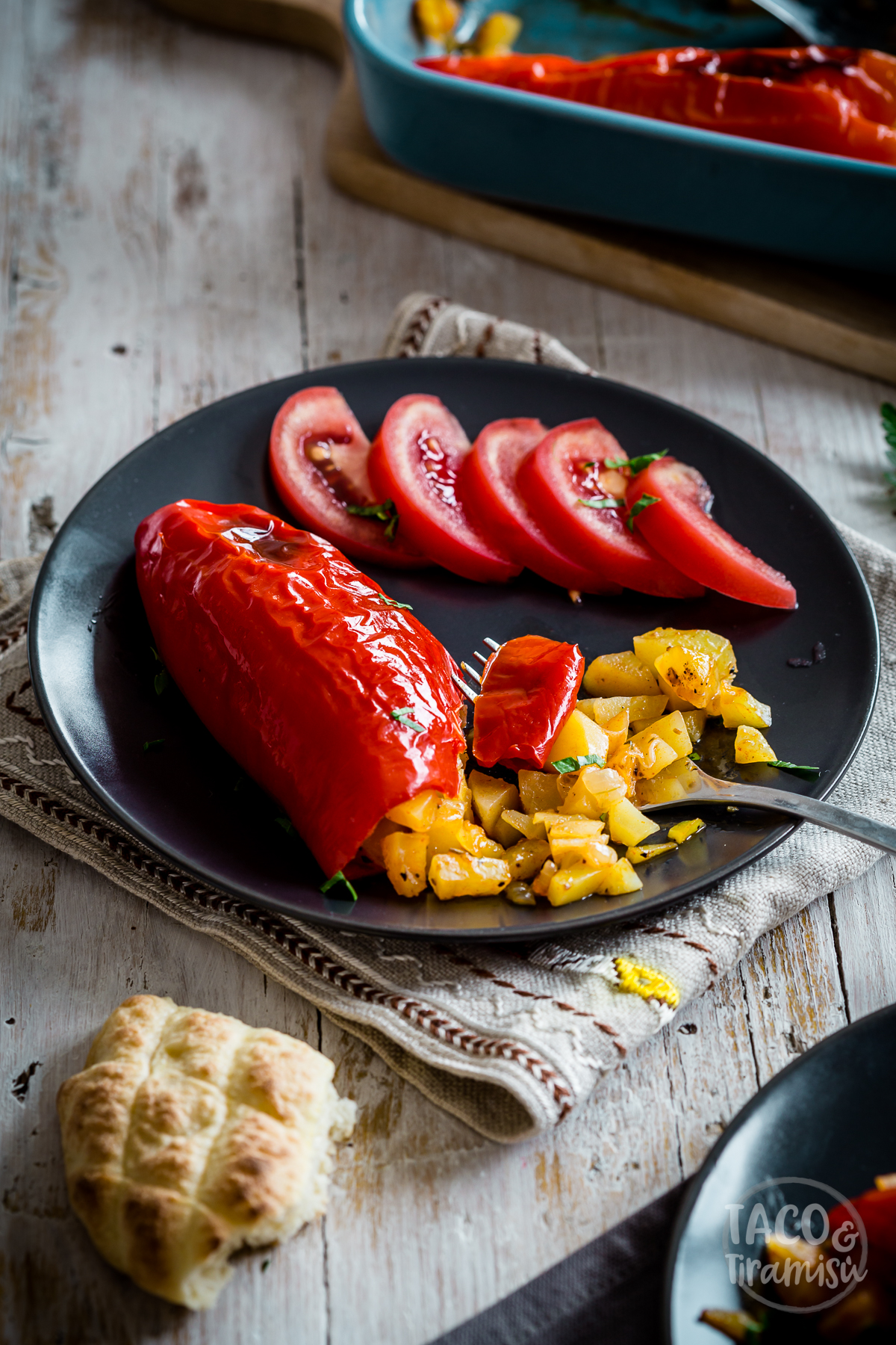 potato stuffed pepper on a plate with tomato slices aside being eaten with a fork