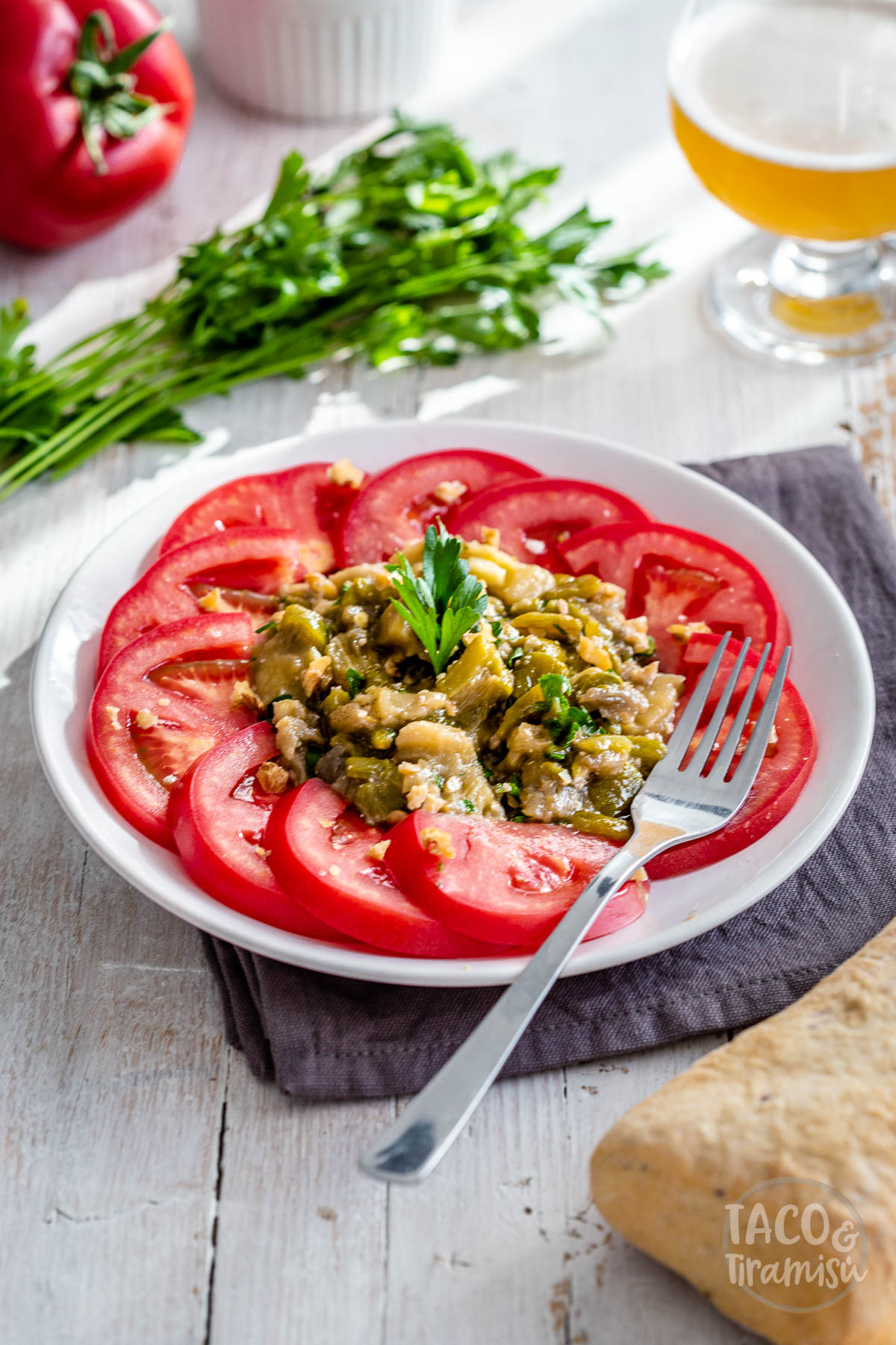 eggplant-pepper salad on a plate with a fork and vegetables aside