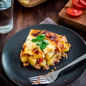 potato moussaka on a plate with a fork