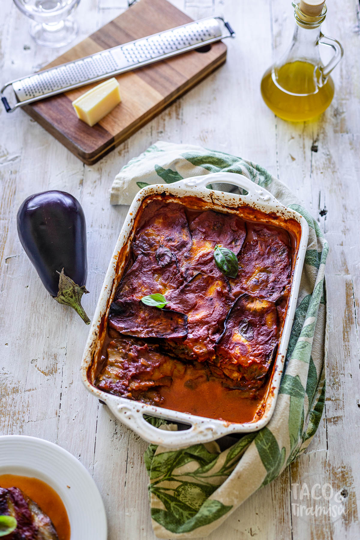 eggplant parmigiana on a white table with olive oil, an eggplant and parmesan aside