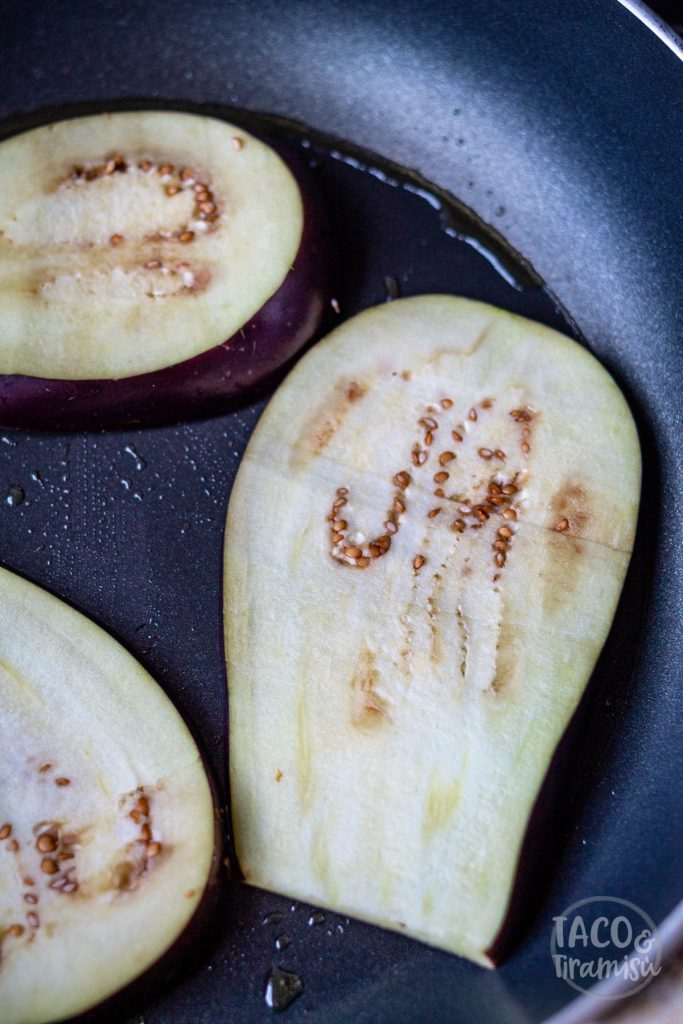 eggplants being cooked on a pan