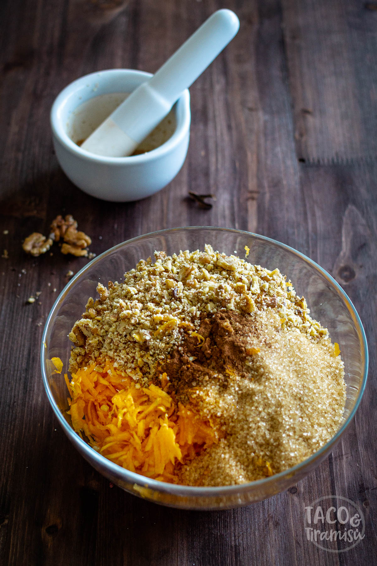 grated pumpkin, sugar, walnuts and spices in a bowl
