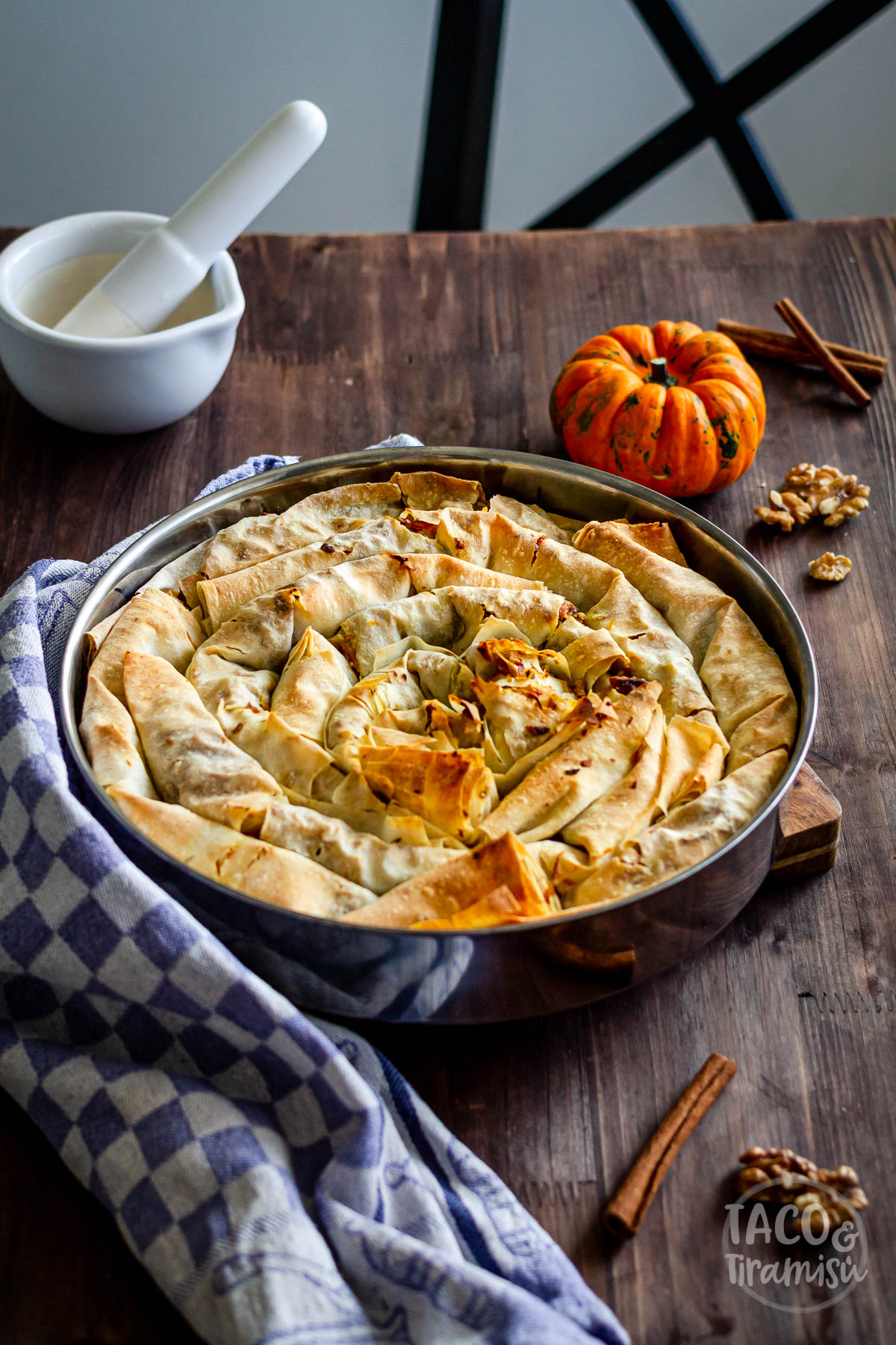 pumpkin banitsa on a wooden background with mortar and pestle aside