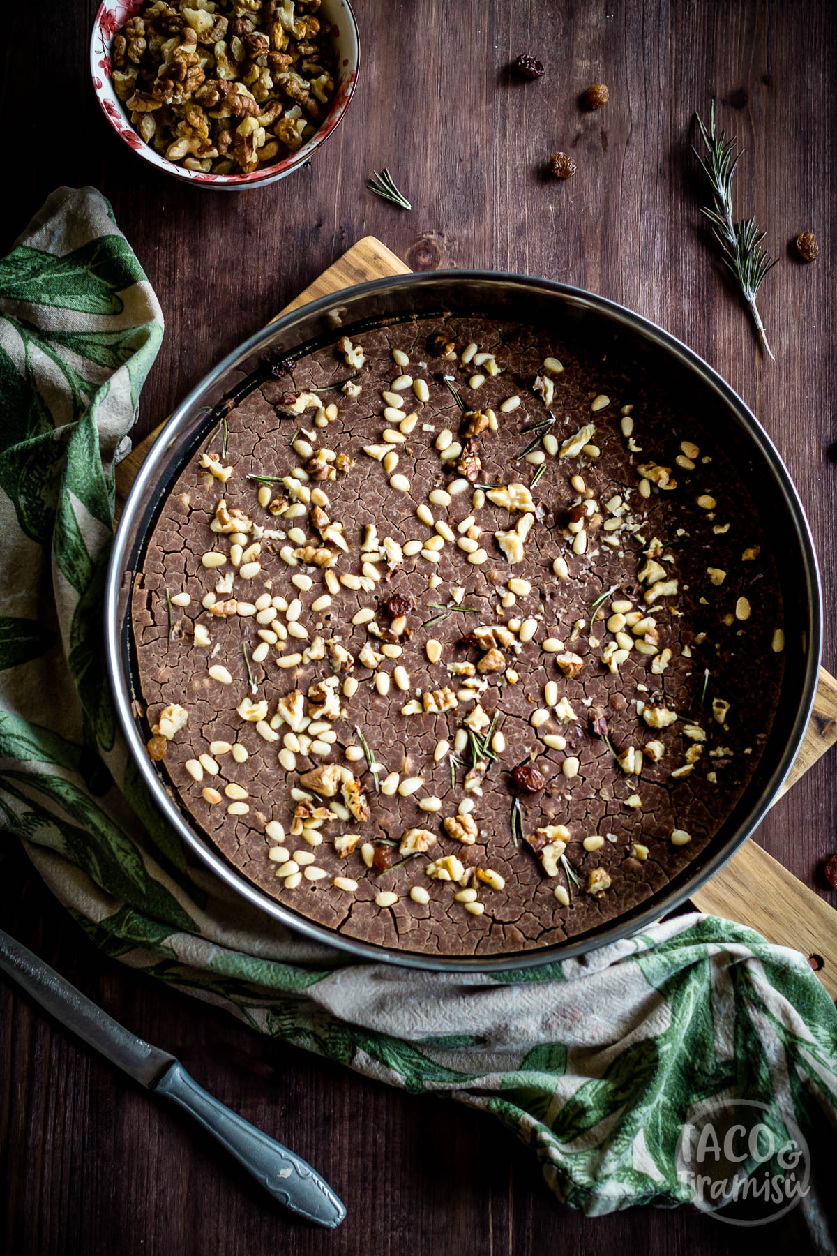 castagnaccio in a pan with nuts aside, flat lay