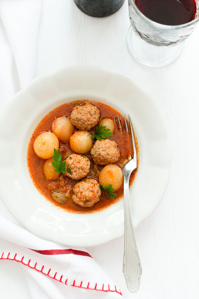 Meatball stew with pearl onions served in a white plate with wine aside