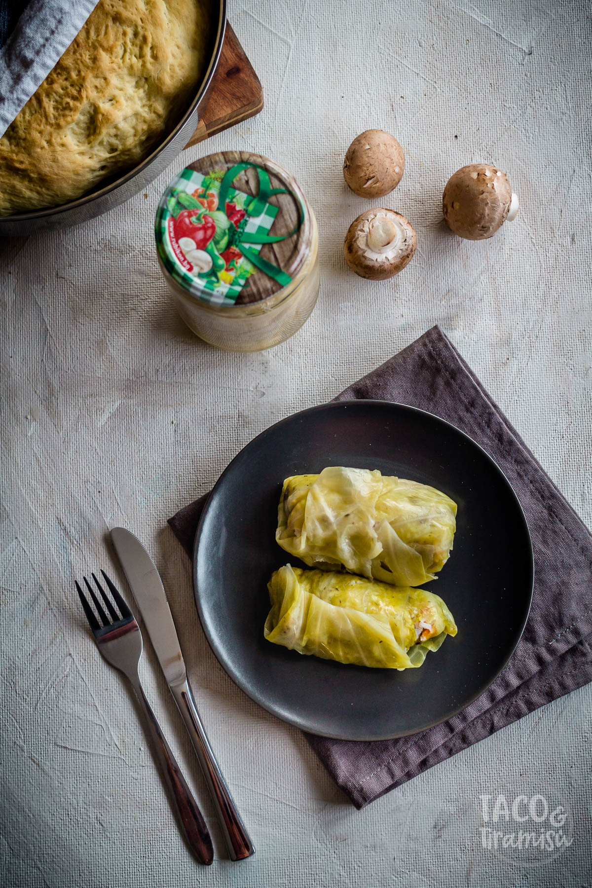 two cabbage rolls on a dark plate with bread and vegetables aside