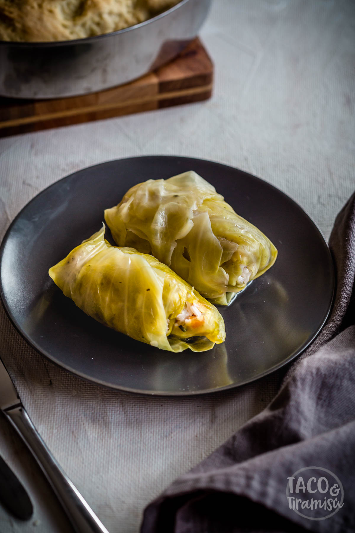 two cabbage rolls on a dark plate