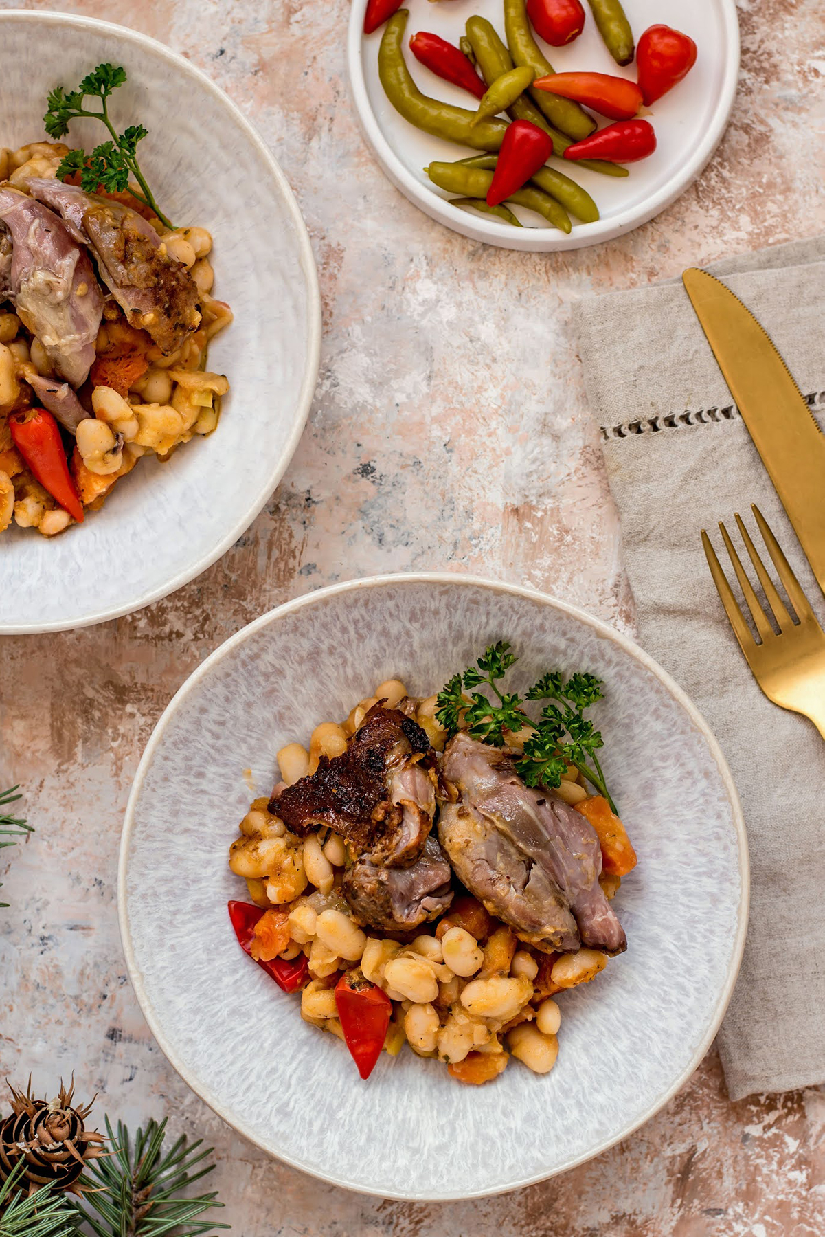 beans with pork shank served in plates with peppers aside