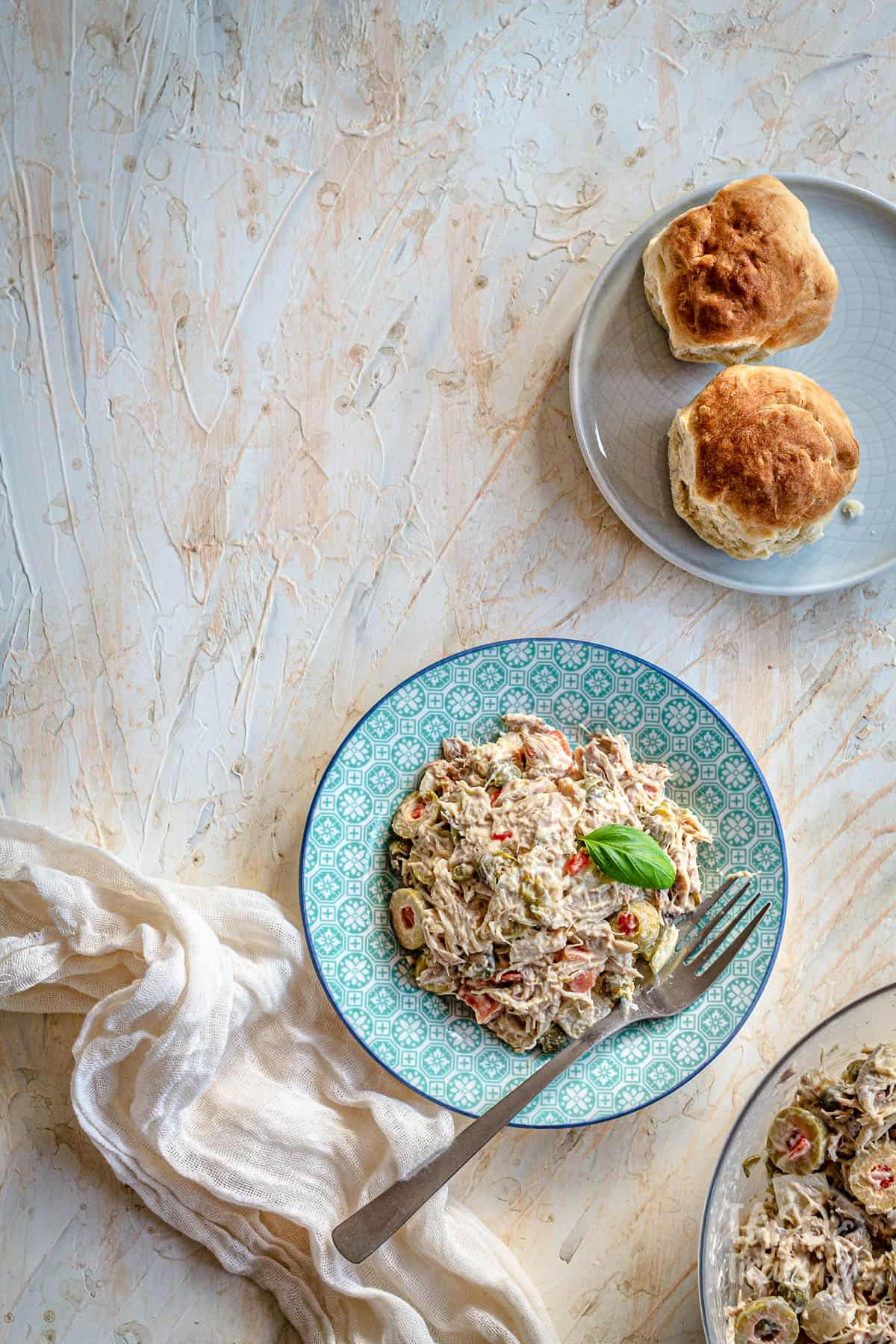 a plate of chicken salad with a fork inside and bread rolls aside