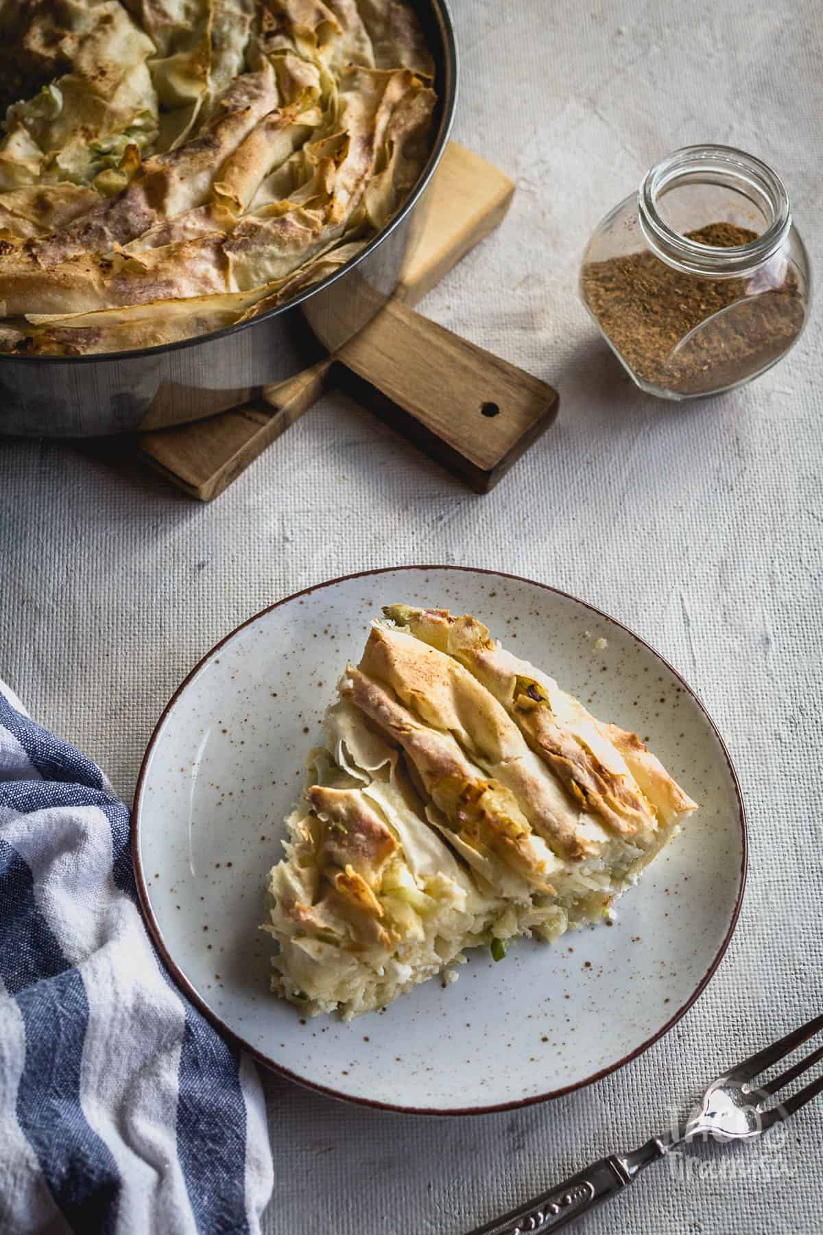 banitsa with a slice taken out and spices aside