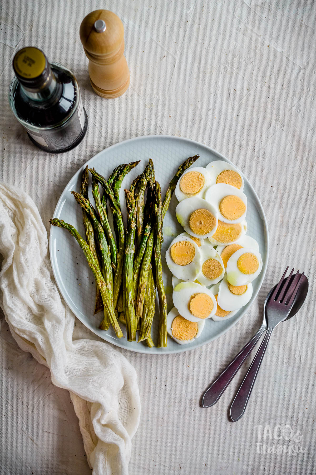 asparagus with eggs served on a plate with vinegar aside