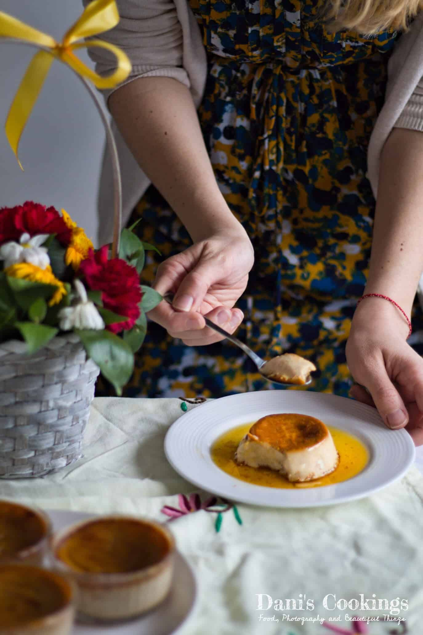 a woman eating creme caramel on a plate next to flowers